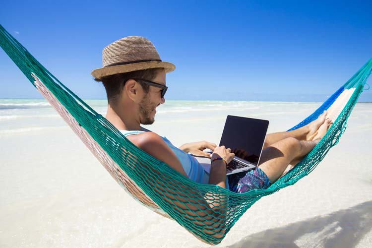 Happy man working remotely with a laptop, on a hammock at the beach.